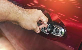 mão humana destrancando a porta do carro na garagem foto