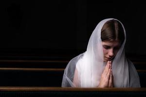 uma jovem modesta com um lenço na cabeça está sentada na igreja e orando foto