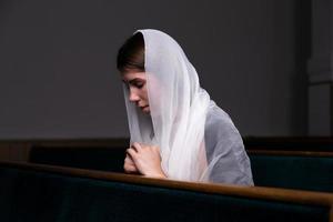 uma menina cristã de camisa branca está orando com o coração humilde na igreja foto