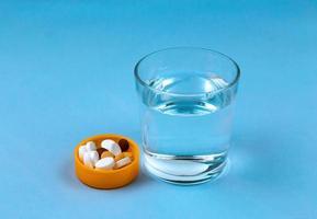 copo de água e comprimidos em fundo azul com espaço de cópia para o texto foto