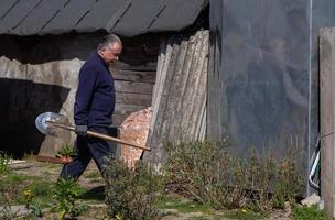 fazendeiro homem adulto carrega uma pá em seu jardim foto