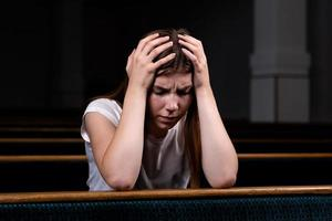 uma triste garota cristã de camisa branca está sentada e orando com o coração humilde na igreja foto