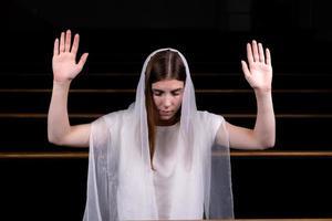 uma menina cristã orando com o coração humilde na igreja foto