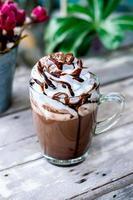 cacau de chocolate quente em caneca de vidro com chantilly foto