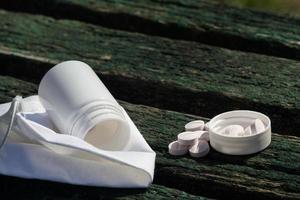 Comprimidos brancos deitados em um banco velho foto