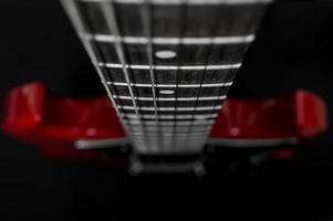 closeup de guitarra elétrica vermelha em fundo preto foto