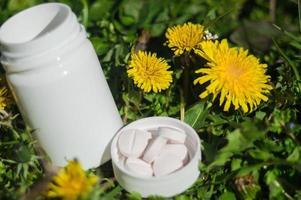 comprimidos brancos na grama com flores foto