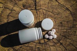 frasco branco e pílulas brancas caídas em um toco foto