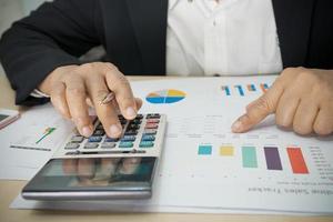 contador asiático trabalhando e analisando relatórios financeiros, contabilidade de projetos com gráfico gráfico e calculadora foto