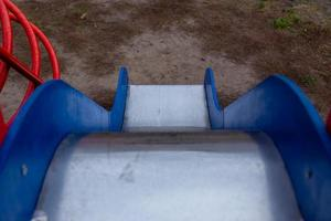 slide infantil com lados azuis e uma superfície de metal brilhante foto