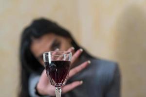 desistindo do álcool uma jovem na mesa recusa uma taça de vinho tinto com a mão foto