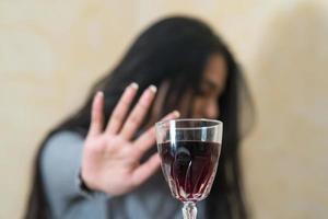 desistindo do álcool, uma jovem à mesa recusa com a mão uma taça de vinho tinto com foco seletivo foto
