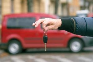 Novo conceito de carro mão masculina segurando a chave do carro foto