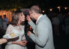 a noiva e o noivo na festa cortam e experimentam o bolo de casamento foto
