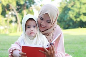 mãe muçulmana ensina a filha a ler alegremente o Alcorão no parque no verão foto