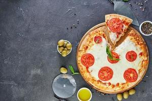 pizza italiana e ingredientes para cozinhar em um fundo de concreto preto tomates azeitonas manjericão e especiarias foto