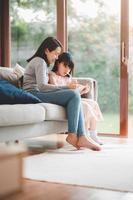 mãe e filha usando tablet digital para estudar juntas foto
