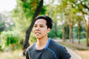 homem asiático em fitness wear ruuning no parque foto