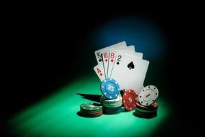 cartas de pôquer e fichas de jogo em um feixe de luz em um fundo escuro com espaço de cópia foto