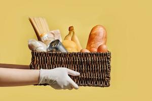cesta de vime com um conjunto de produtos nas mãos em luvas de proteção isoladas em um fundo amarelo foto