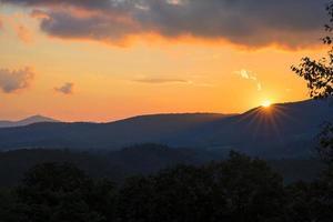 o sol se põe abaixo do horizonte no cume azul foto