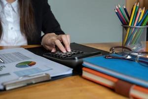 mulher de negócios ou contadores estão trabalhando no escritório para verificar a exatidão da conta usando calculadora para calcular para análise de dados foto