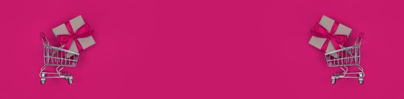carrinhos de supermercado e caixas de presente em fundo rosa com banner amplo de conceito de compras de espaço de cópia foto