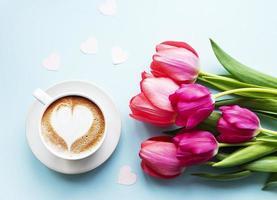 xícara de café com latte art e tulipas foto