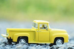 Desfocar brinquedos de caminhão amarelos com fundos de luz verde bokeh foto