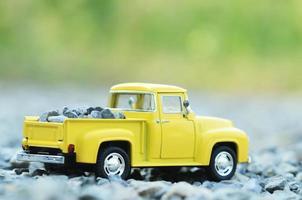 brinquedos de caminhão amarelos com fundo de luz verde bokeh foto