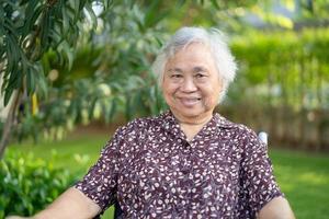 idoso asiático idoso ou idosa senhora paciente sorrindo em cadeira de rodas foto