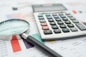 lupa e calculadora em papel de gráficos de tabelas foto
