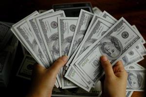 mãos segurando notas de dinheiro 100 usd foto