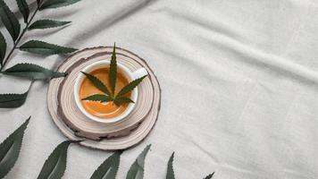 folha de cannabis em uma xícara de café em uma toalha de mesa branca foto