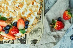 Bolo de merengue de morango com pétalas de amêndoa no jornal foto