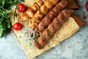 pratos de carne com churrasco e kebab em fundo cinza foto