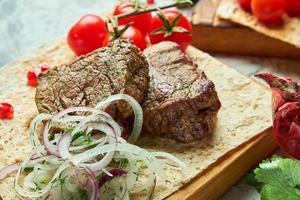 tábua de madeira com carne de churrasco foto