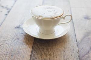 cappuccino quente em fundo de madeira foto