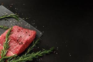 pedaço de carne com pimenta alecrim e sal em um fundo escuro com espaço de cópia foto