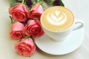 cappuccino em copo branco com cinco rosas em fundo de papel foto