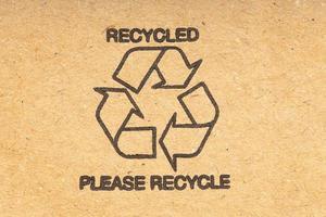 símbolo de reciclagem em fundo marrom de papelão reciclado foto
