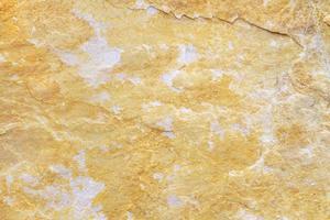 textura de fundo de pedra natural com tons de amarelo bege e cinza foto