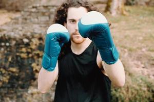 um jovem de cabelo comprido fazendo boxe e artes marciais no parque com luvas de boxe e cara séria foto