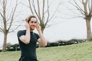 um jovem atlético usando fones de ouvido enquanto faz exercícios no parque com espaço de cópia foto
