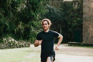 um homem de cabelo comprido correndo entre as árvores durante um dia ensolarado no parque foto