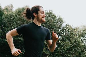 um super close de um homem treinando no parque enquanto sorri foto