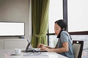 mulher segurando um telefone inteligente com o ombro e digitando no teclado do laptop foto