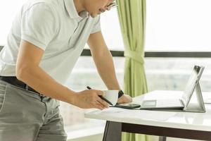 empresário verificando e-mail no laptop e segurando uma xícara de café foto