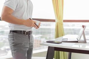 empresário trabalhando com laptop e segurando uma xícara de café foto
