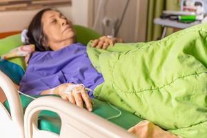 mão do paciente sênior com injeção de solução salina deitada na cama do hospital foto